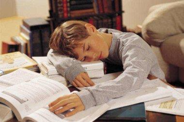 перегруженный домашними заданиями школьник